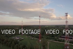 View of forest, country houses and base stations against blue sky with clouds in daylight at summer, Russia