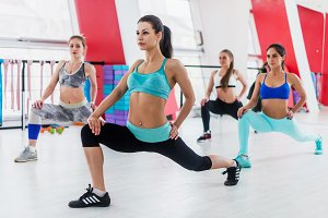 Young women taking group fitness classes doing lunges in modern sports club