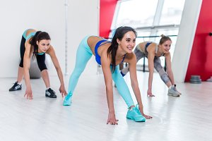 Smiling pretty young sportswomen stretching doing single leg forward bend exercise during group fitness training in light modern gym
