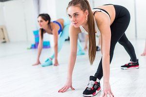 Pretty slim girl wearing sportswear taking part in group fitness classes stretching her legs and back by doing bend exercise with straight legs indoors in sports club