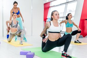 Group of women doing kneeling quads stretch exercise while fitness instructor helping in the background in studio