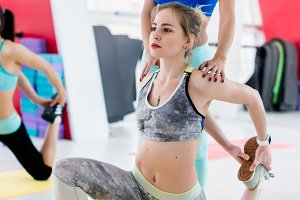 Personal instructor helping slim young girl to do leg stretching exercise in light modern fitness center