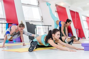 Professional young female athletes warming-up doing different stretching exercises in sport club for women
