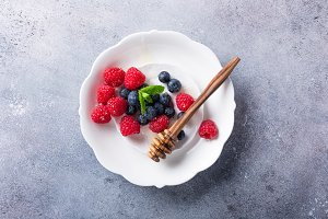 Freshly picked blueberries and raspberries on white plate
