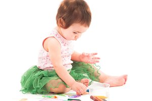 Toddler girl paints on the paper