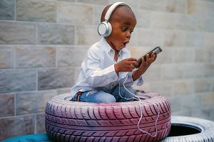 A bold boy listening to music inside a tire