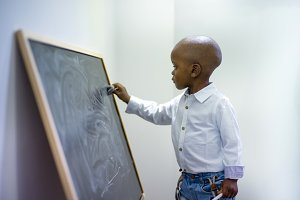 A black child cleaning a blackboard