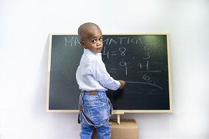 A black child writing on a blackboard