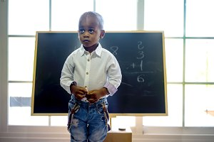 A black child in front of a blackboard