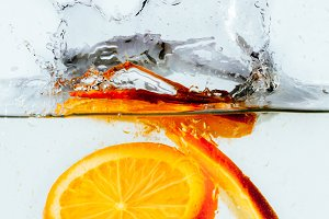 orange halves falling into water on white background