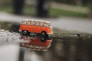 Orange Vintage Model Bus in Puddle