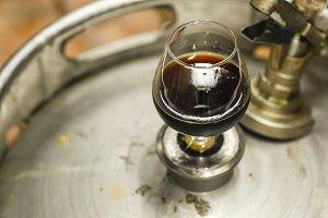 Glass of stout on a keg