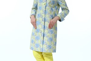 business woman with pony tail in casual over coat and yellow trousers full body length