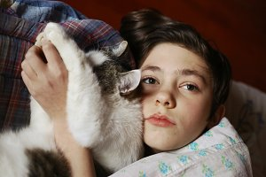 teenager boy in bed with cat cullde
