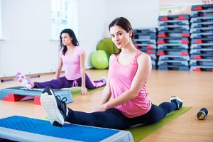 Flexible fit women stretching legs with aerobic step platforms.