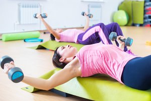 Fit women lifting dumbbell while lying on step platforms.