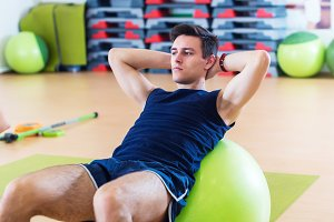 Fit man doing sit-ups on exercise balls.