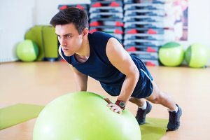 Fit man exercising with  ball workout out arms Exercise training triceps and biceps doing push ups.