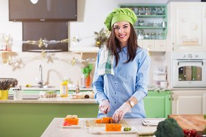 Female cook wearing Chef s hat and gloves making Japanese sushi rolls, smiling, looking at camera in the kitchen