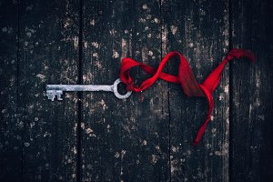 an antique rusty key on red ribbon on vintage wooden board