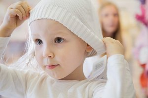 Child's dress store - little blonde baby girl with mother doing shopping and buying hat