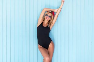 sexy blonde woman in bodysuit with perfect body wearing sunglasses and cap standing near wall