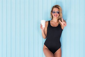 Beauty woman portrait Beautiful girl in bodysuit looking and showing v-sign peace or victory gesture at camera holding cup of coffee take away.