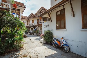 Bangkok old city view, Thailand. Small rural road with traditional houses, green lush trees and parked motorbike at sunny day, outdoor city landscape