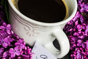 Cup of coffee and lilac flowers