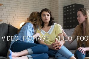 Two young woman bear up and calm down their best friend who is upset and depressed