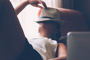 Woman sleeping with hat on face