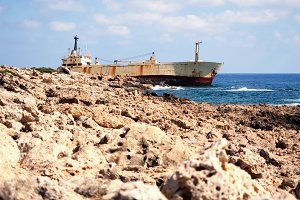 Ship on the rocks near the rocky shore. Paphos, Cyprus