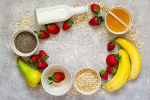 Healthy breakfast ingredients: Oatmeal, honey, fruit, strawberry