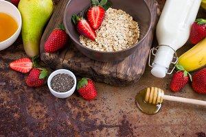 Healthy breakfast ingredients: Oatmeal, honey, fruit, strawberry