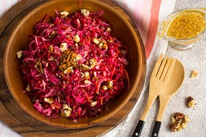 Cabbage beetroot carrot salad with nuts  in a wooden bowl closeu