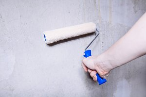 man's hand using paint roller