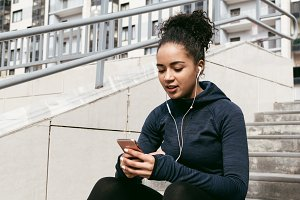 Young female runner using phone