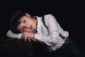 Pensive boy on black background