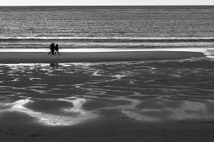 3 persons walking on the beach B&W