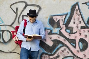 portrait of young man with hat to the urban fashion with the book