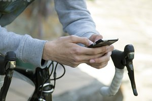 young man with the mobile phone and the bike