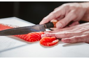 Close up on slicing raw salmon with sharp knife