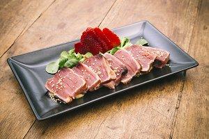 Tuna tataki dish on rustic wooden table