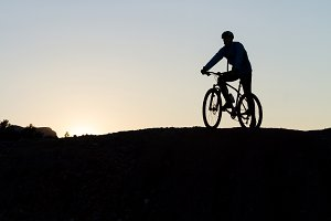 Silhouette of a cyclist on the top