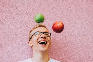 Happy man juggles with apples