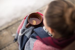 Girl in rug drinks hot tea in winter