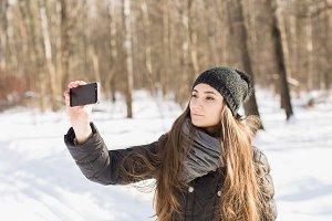 The girl makes selfie in winter
