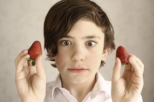 preteen boy acting grimacing with two strawberries