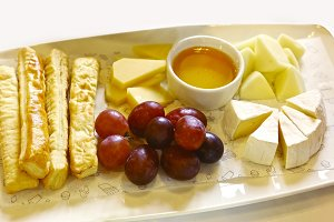 cheese plate with honey saucer grapes