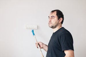 Man paints a wall in white